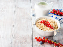 Raw rolled oats with fresh berries on wooden table Royalty Free Stock Photo
