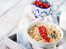 Raw rolled oats with fresh berries on wooden table Royalty Free Stock Images
