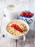 Raw rolled oats with fresh berries on wooden table Stock Images