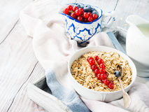Raw rolled oats with fresh berries on wooden table Royalty Free Stock Photography