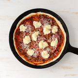 Raw round pizza with salami, onion, mozarella in cast iron skill Royalty Free Stock Photos