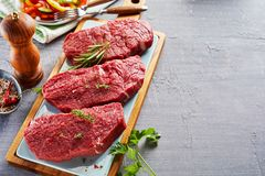Raw rump steak cut in slices on cutting board. Slices of raw rump steak prepared with spices on wooden cutting board Royalty Free Stock Images