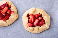 Raw rustic strawberry galettes. Before baking, selective focus, top view Royalty Free Stock Photo