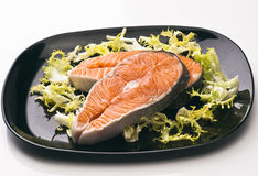 Raw salmon. Wheels black tray, with the leaves of salad stock images
