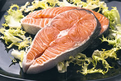 Raw salmon. Wheels black tray, with the leaves of salad royalty free stock photography