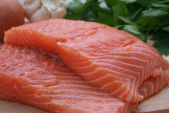 Raw salmon. Fillets of raw salmon with other ingredients in background royalty free stock photo