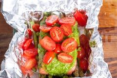 Preparation of salmon with pesto, tomatoes, asparagus Stock Photo