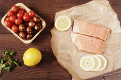Raw salmon on baking paper, cherry tomatoes, lemon and parsley Stock Photography