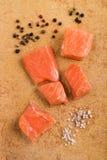 Raw salmon chunks with coarse salt and black peppercorn Stock Image