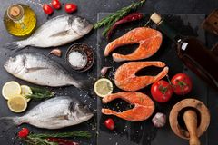 Raw salmon and dorado fish fillet. Raw salmon fish fillet and dorado fish with spices cooking on cutting board. Top view Royalty Free Stock Photos