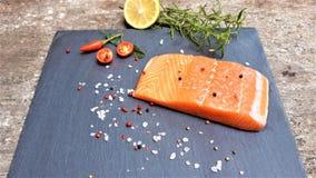 Raw salmon filet on dark slate background stock photography