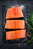 Raw salmon filet on dark slate background, wild atlantic fish, space for text Stock Photos
