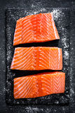 Raw salmon filet on dark slate background, wild atlantic fish Royalty Free Stock Photos