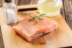 Raw salmon filet on wooden cutting board Stock Photo