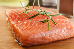 Raw salmon filet on wooden cutting board Royalty Free Stock Photos
