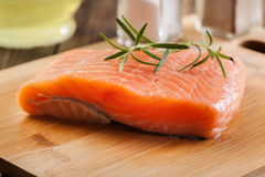 Raw salmon filet on wooden cutting board Stock Images