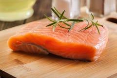 Raw salmon filet on wooden cutting board. Fresh raw salmon filet on wooden cutting board Stock Images