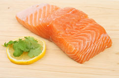 Raw salmon fillet. Raw fillet of salmon with lemon and coriander garnish on a wooden board Stock Images