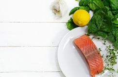 Raw salmon fillet with aromatic herbs, garlic, lemon and spinach. Preparing raw salmon fillet with aromatic herbs, garlic, lemon and spinach on a white wooden Royalty Free Stock Image