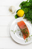 Raw salmon fillet with aromatic herbs, garlic, lemon and spinach. Preparing raw salmon fillet with aromatic herbs, garlic, lemon and spinach on a white wooden Royalty Free Stock Photos