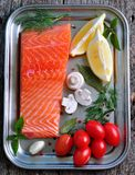 Raw salmon fillet with cherry tomato, mushroom, dill, garlic, lemon and sea salt Royalty Free Stock Photo