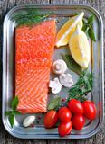 Raw salmon fillet with cherry tomato, mushroom, dill, garlic, lemon and sea salt Royalty Free Stock Images