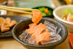 Raw salmon fillet. Chopsticks gripping raw salmon fillet from the bowl Royalty Free Stock Photo