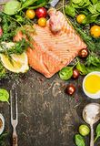 Raw salmon fillet with delicious fresh aromatic herbs, spices, vegetables ,lemon and oil on rustic wooden background, top view. Place for text Royalty Free Stock Images