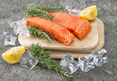 Raw salmon fillet with fresh herbs. Seafood. Fish. Raw salmon fillet with fresh herbs, lemon and ice. Seafood. Fish. Healthy nutrition Stock Photo