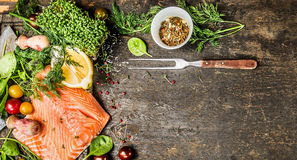 Raw salmon fillet with fresh seasoning, spices and fork on rustic wooden background, top view, banner for website stock image