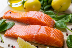 Raw Salmon Fillet. Fresh Salmon Steaks with Lemons and Baby  Spinach  on a Cutting Board Stock Photo