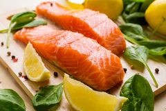 Raw Salmon Fillet. Fresh Salmon Steaks with Lemons and Baby  Spinach  on a Cutting Board Stock Photos