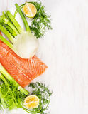 Raw salmon fillet with green herbs and lemon on white wooden Stock Photos