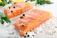 Raw salmon fillet with herbs and spices. Ready for baking on stone background Stock Photography
