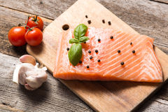 Raw salmon fillet with herbs. On wooden background Stock Photos