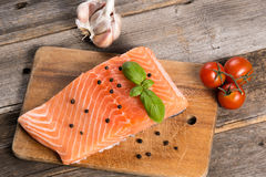 Raw salmon fillet with herbs. On wooden background Stock Photography