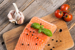 Raw salmon fillet with herbs. On wooden background Royalty Free Stock Images