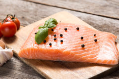 Raw salmon fillet with herbs. On wooden background Royalty Free Stock Photography