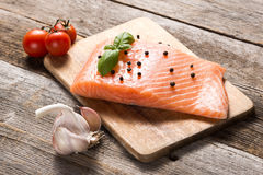 Raw salmon fillet with herbs. On wooden background Royalty Free Stock Photos