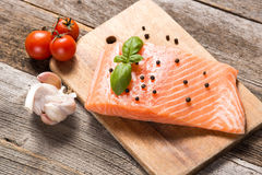 Raw salmon fillet with herbs. On wooden background Royalty Free Stock Image