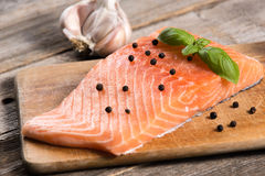 Raw salmon fillet with herbs. On wooden background Royalty Free Stock Photo