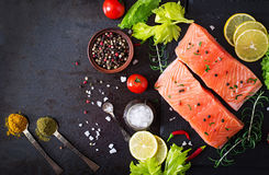 Raw salmon fillet and ingredients for cooking on a dark background in a rustic style. Royalty Free Stock Photos