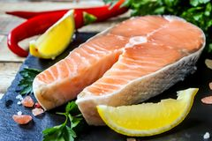 Raw salmon fillet and ingredients for cooking. On a dark cutting board on rustic wooden background. Selective focus Stock Photos