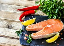 Raw salmon fillet and ingredients for cooking. On a dark cutting board on rustic wooden background. Selective focus Royalty Free Stock Image