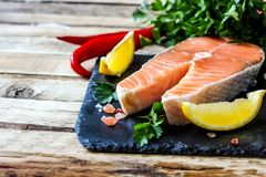 Raw salmon fillet and ingredients for cooking. On a dark cutting board on rustic wooden background. Selective focus Stock Images