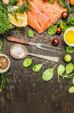Raw salmon fillet with ingredients for cooking, fork and spoon with salt on rustic wooden background, top view. Place for text Stock Photos