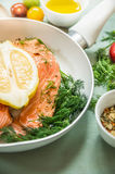 Raw salmon fillet  with lemon and fresh dill, preparation in white frying pan. Close up Stock Photo