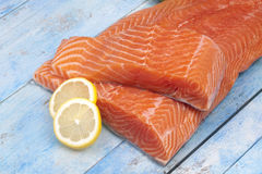 Raw salmon fillet and lemon slices on blue wooden table Stock Photo