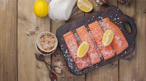 Raw salmon fillet with pepper sweetbread and salt on baking paper rustic theme with copy-space. Flat lay.  stock photo