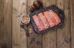 Raw salmon fillet with pepper sweetbread and salt on baking paper rustic theme with copy-space. Flat lay.  Stock Photos